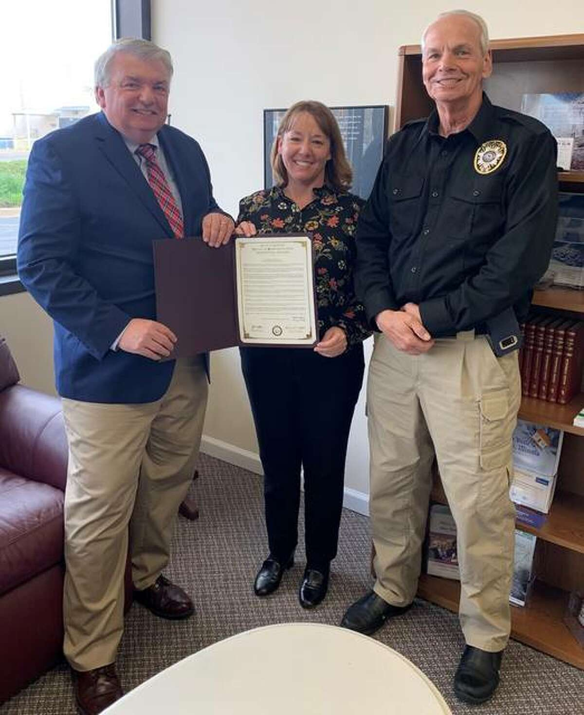 Former Madison County Chief Deputy Coroner Roger D. Smith, left, receives a copy of House Resolution 154 congratulating him on his reetirement from state Rep. Amy Elik, R-Fosterburg. At right is Madison County Coroner Steve Nonn.