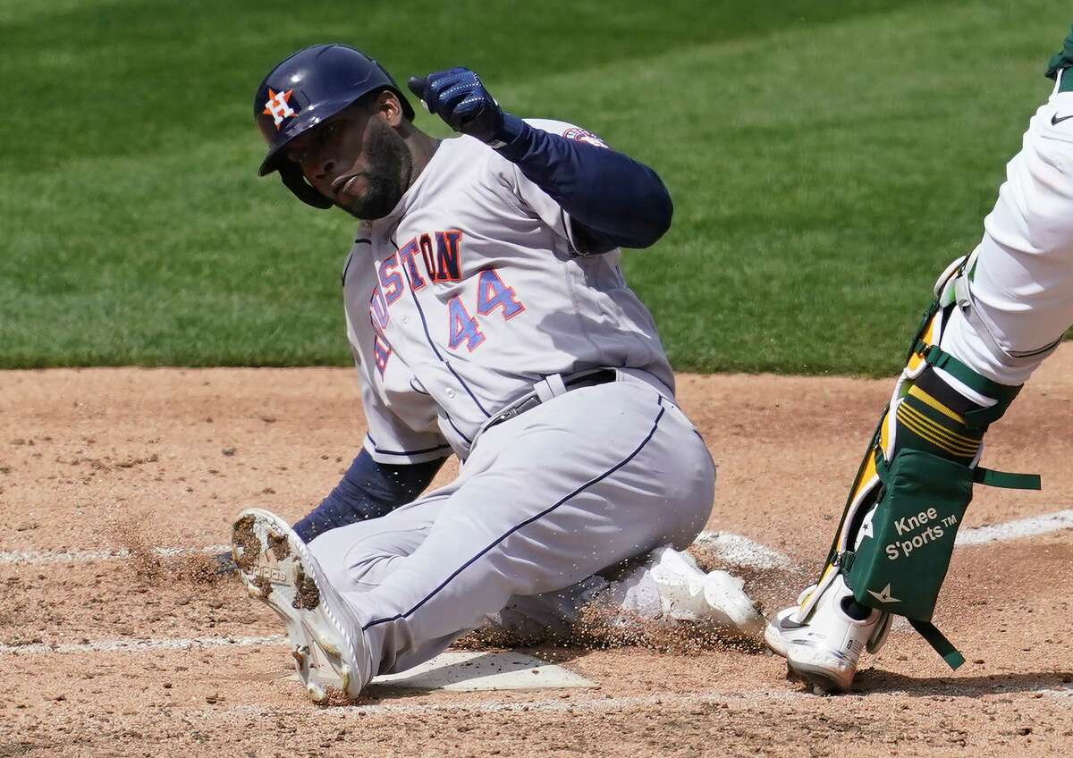 Astros designated hitter Yordan Alvarez slides across the plate after running from first to home during Sunday's 9-2 victory at Oakland.