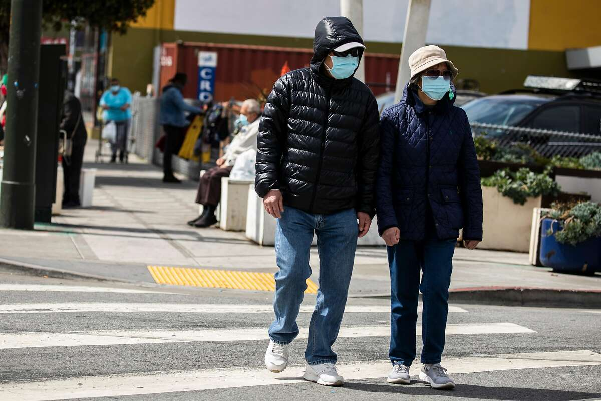 Masked pedestrians walk along Mission Street in the Excelsior district amid the ongoing COVID-19 pandemic in San Francisco, California Wednesday April 7, 2021.