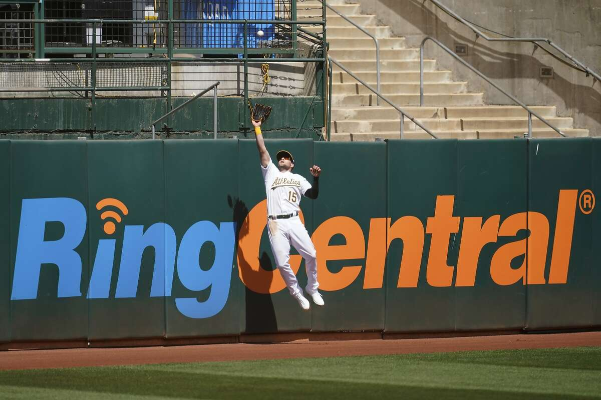 Oakland Athletics left fielder Seth Brown catches a fly out hit by Los Angeles Dodgers' Austin Barnes during the fourth inning of a baseball game in Oakland, Calif., Wednesday, April 7, 2021. (AP Photo/Jeff Chiu)
