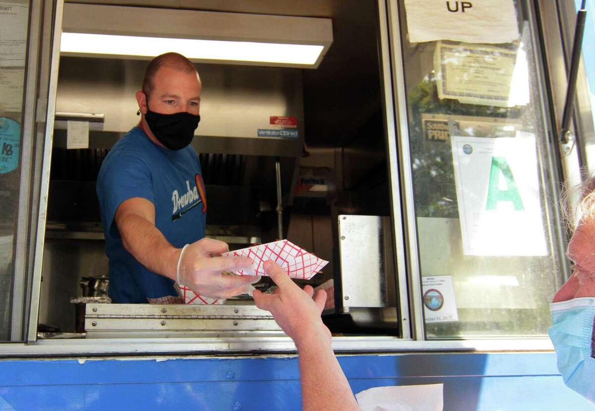 Drew Kaplan, with the DrewbaQ food truck, serves a customer in September. DrewbaQ earned a 96 on the March health inspection.
