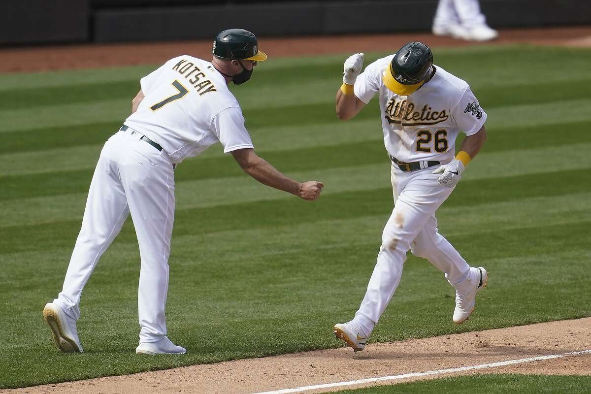 Matt Chapman is congratulated by third base coach Mark Kotsay after hitting a solo home run in the seventh inning.