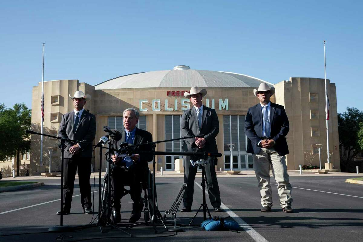 Flanked by Texas Rangers, Gov. Greg Abbott speaks Wednesday in front of the Freeman Coliseum, where a temporary facility has been set up to house unaccompanied migrant minor boys. The governor called on the federal government to shut down the facility, saying two state agencies had received complaints Wednesday morning alleging child abuse and neglect.