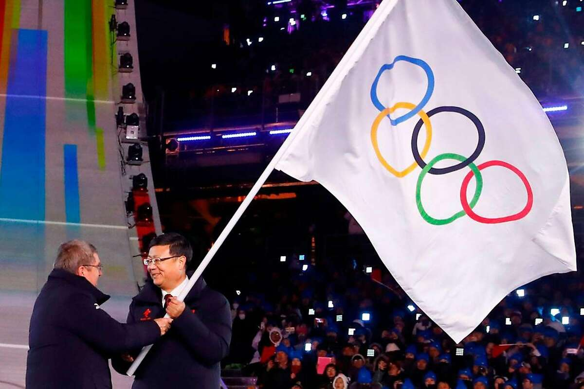 Thomas Bach, left, president of the International Olympic Committee, passes the flagpole during the handover ceremony of the Olympic flag to the mayor of Beijing, Chen Jining, who will host the 2022 Beijing Winter Olympic Games during the closing ceremony of the Pyeongchang 2018 Winter Olympic Games at the Pyeongchang Stadium on Feb. 25, 2018. (Kai Pfaffenbach/AFP via Getty Images/TNS)
