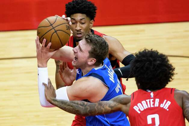 Dallas Mavericks guard Luka Doncic (77) drives between Houston Rockets center Christian Wood (35) and Houston Rockets guard Kevin Porter Jr. (3) during the first quarter of an NBA game between the Houston Rockets and Dallas Mavericks on Wednesday, April 7, 2021, at Toyota Center in Houston. Photo: Mark Mulligan, Staff Photographer / © 2021 Mark Mulligan / Houston Chronicle