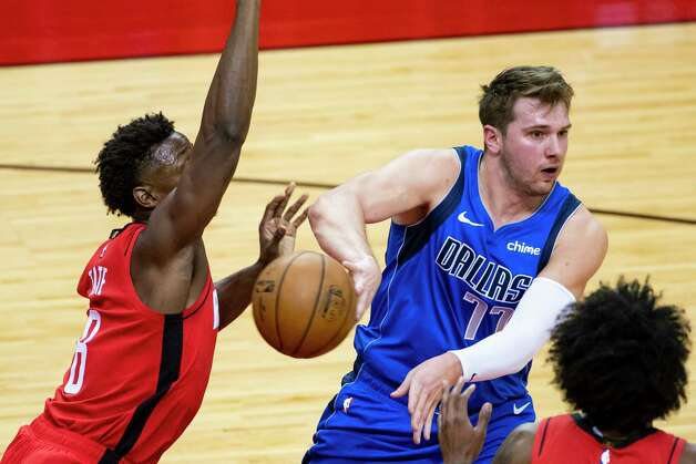 Dallas Mavericks guard Luka Doncic (77) passes past Houston Rockets forward Jae'Sean Tate (8) during the first quarter of an NBA game between the Houston Rockets and Dallas Mavericks on Wednesday, April 7, 2021, at Toyota Center in Houston. Photo: Mark Mulligan, Staff Photographer / © 2021 Mark Mulligan / Houston Chronicle