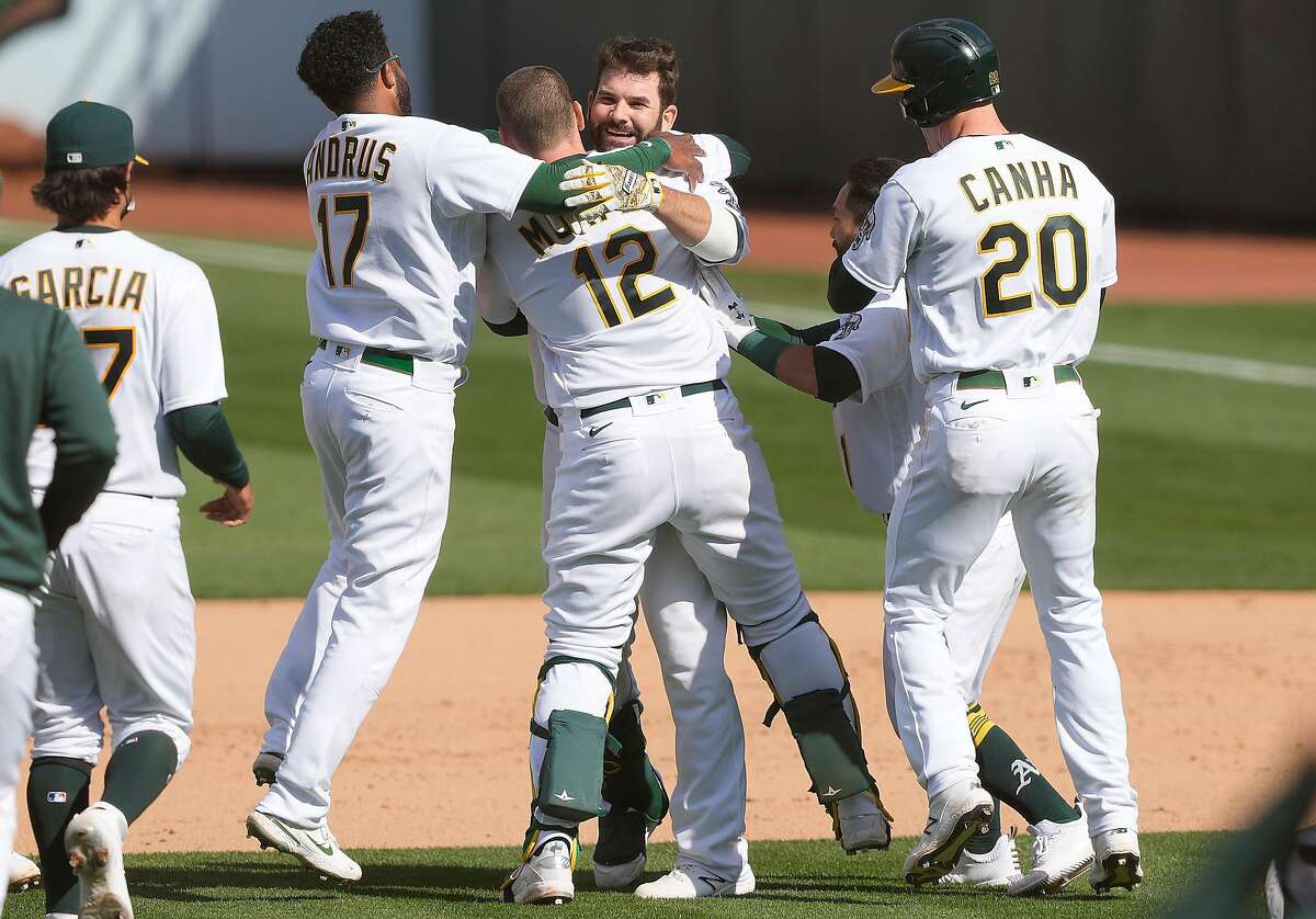 Mitch Moreland (12) celebrates good times Wednesday with his teammates after his game-winnng hit at the Coliseum.