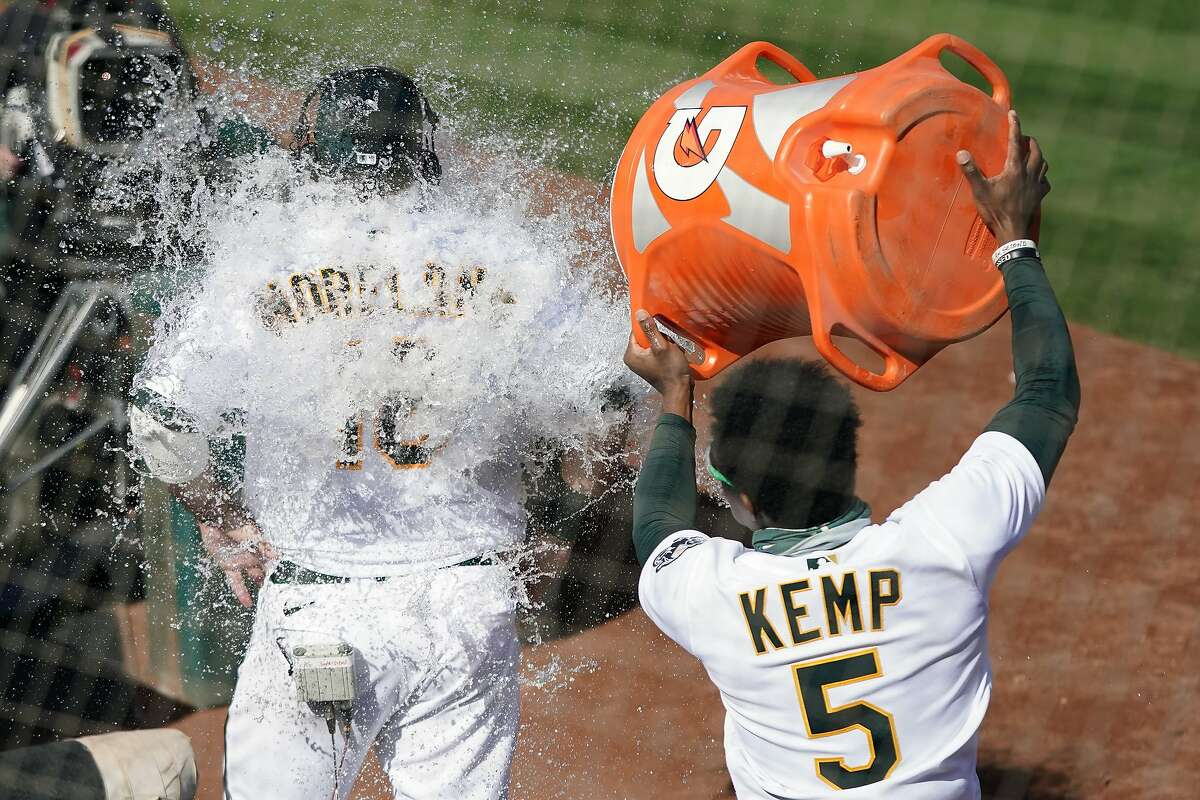 Tony Kemp dumps water onto the back of Mitch Moreland, who had just driven in the winning run in the 10th inning.