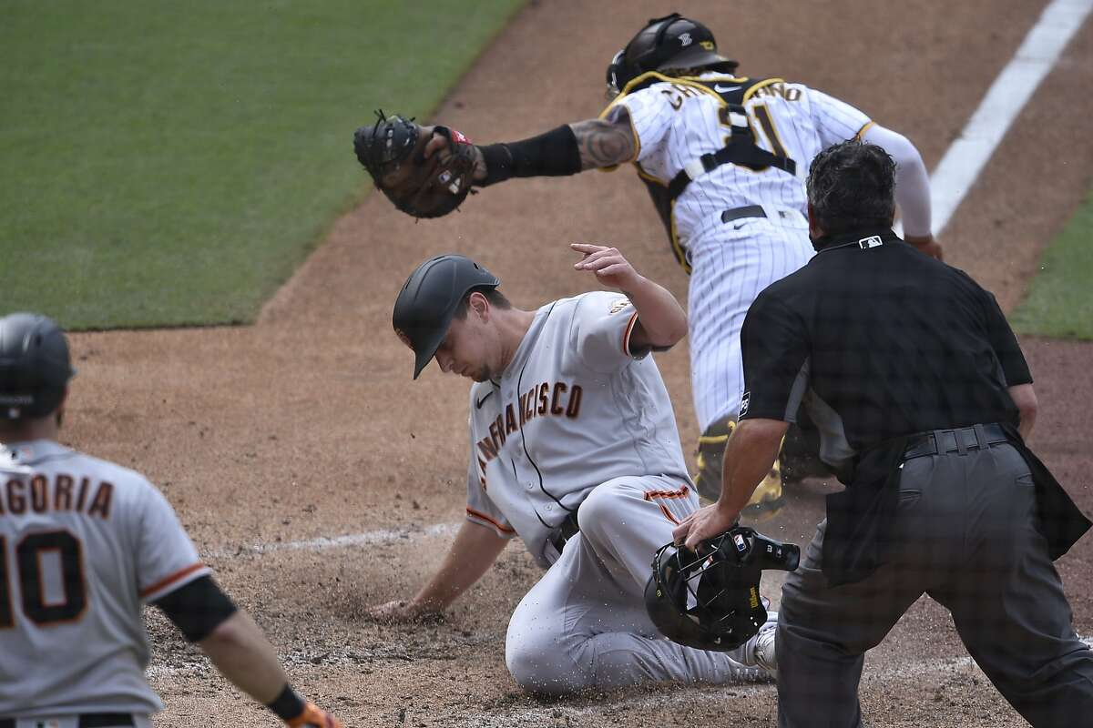 Alex Dickerson slides into home ahead of the tag by Padres catcher Luis Campusano for the go-ahead score in the 10th.