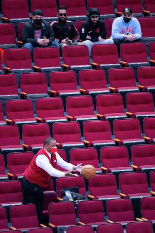 An usher retrieves a ball from the stands during the second quarter of an NBA game between the Houston Rockets and Dallas Mavericks on Wednesday, April 7, 2021, at Toyota Center in Houston. Photo: Mark Mulligan, Staff Photographer / © 2021 Mark Mulligan / Houston Chronicle