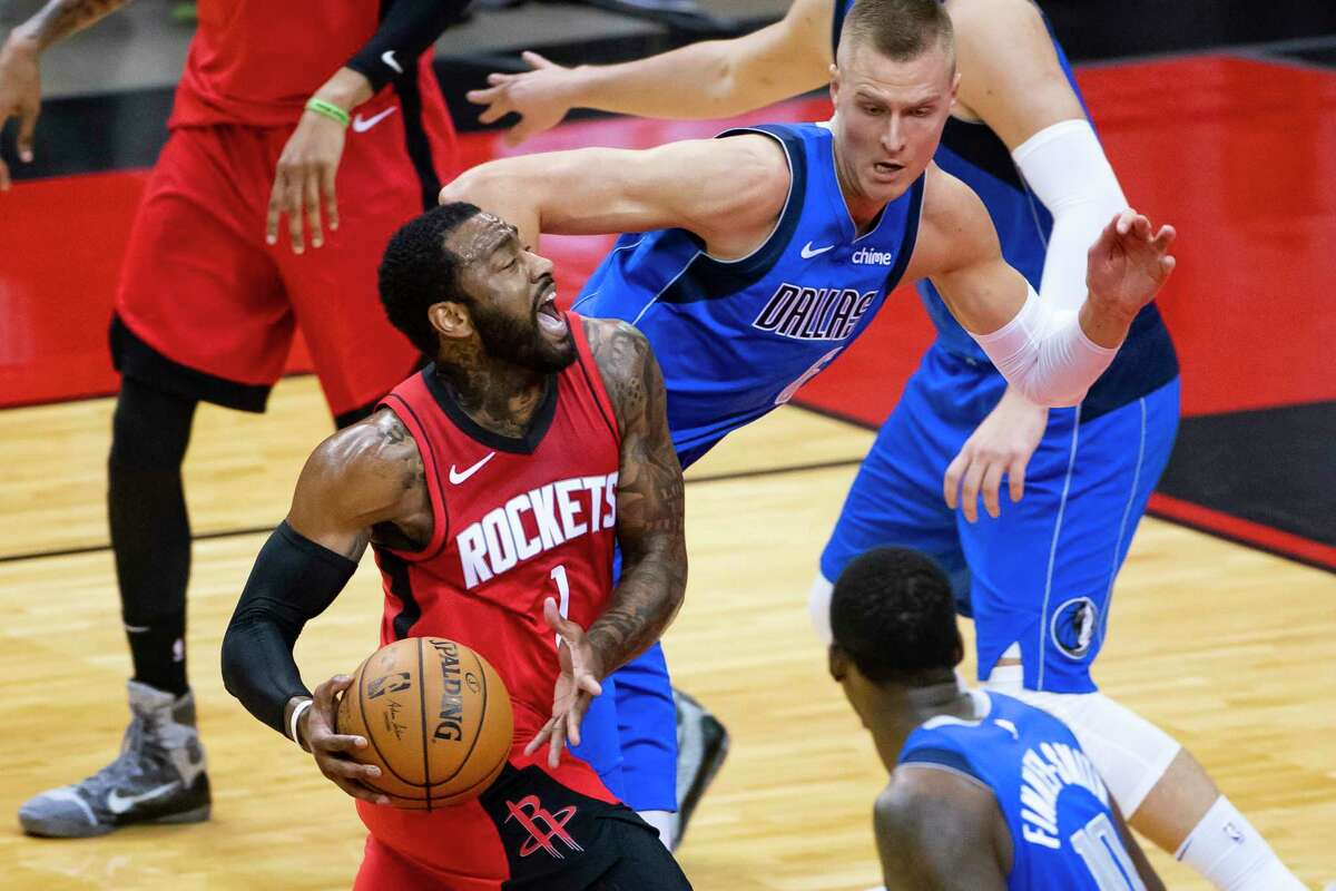 Houston Rockets guard John Wall (1) drives past Dallas Mavericks center Kristaps Porzingis (6) during the second quarter of an NBA game between the Houston Rockets and Dallas Mavericks on Wednesday, April 7, 2021, at Toyota Center in Houston.