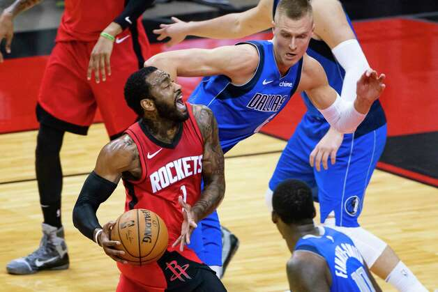 Houston Rockets guard John Wall (1) drives past Dallas Mavericks center Kristaps Porzingis (6) during the second quarter of an NBA game between the Houston Rockets and Dallas Mavericks on Wednesday, April 7, 2021, at Toyota Center in Houston. Photo: Mark Mulligan, Staff Photographer / © 2021 Mark Mulligan / Houston Chronicle