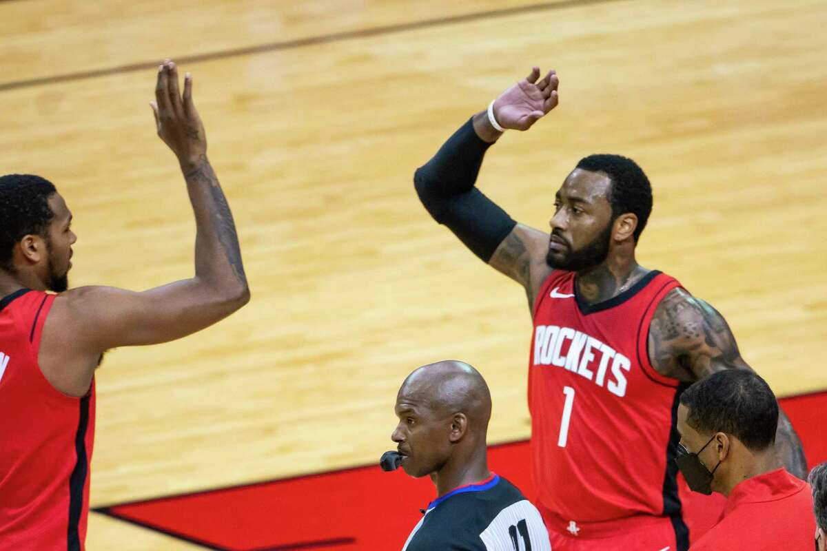 Houston Rockets guard John Wall (1) high fives Houston Rockets forward Sterling Brown (0) during the third quarter of an NBA game between the Houston Rockets and Dallas Mavericks on Wednesday, April 7, 2021, at Toyota Center in Houston.
