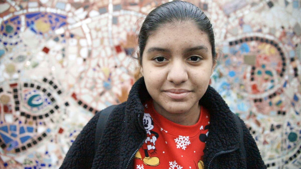 Gabby Espada, 14, lives near the Sixth Avenue altar and tends it as a volunteer for the Sanctuary for Independent Media. Behind her is the glittering mosaic wall that backs Freedom Square's concert stage a few steps away from the altar. Before the pandemic, the stage was a venue for live concerts her entire neighborhood enjoyed.