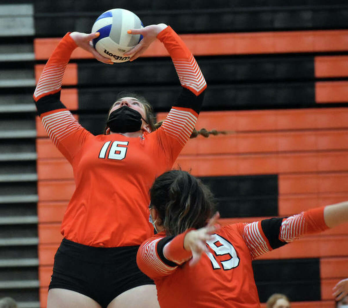 Edwardsville's Lexie Griffin sets a pass for teammate Rhianna Huebner in the first game against Belleville East on Wednesday in Edwardsville.