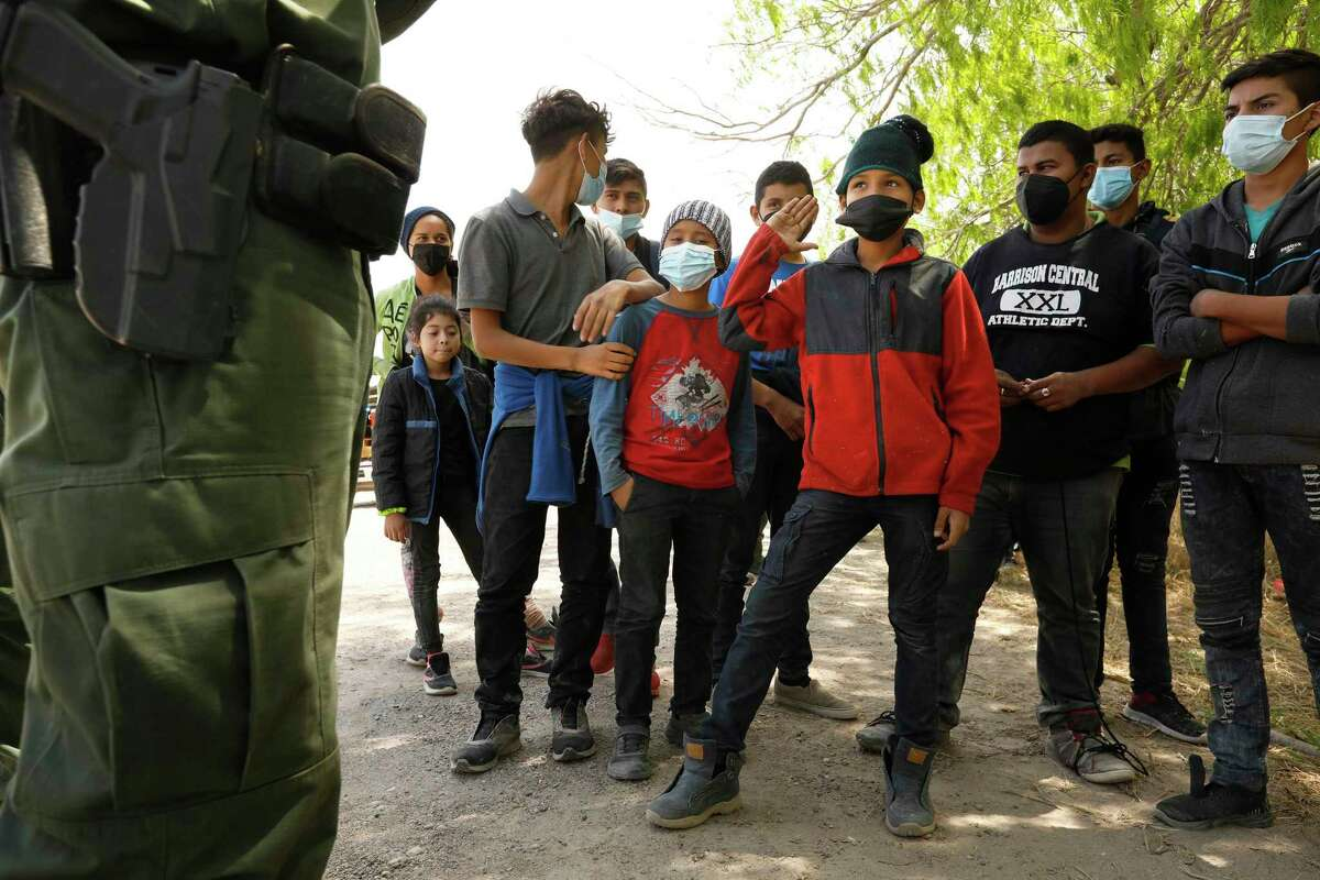 Ten-year-old Christopher Garcia, red shirt second from left, prepares to board a bus with fellow juvenile migrants from Central American to be transported to a Border Patrol holding area on March 25, 2021, in La Joya, Texas. (Carolyn Cole/Los Angeles Times/TNS)