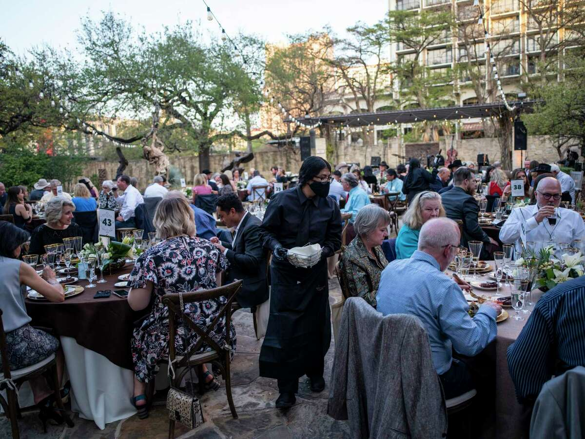 Guests eat dinner before the start of a live auction at the Briscoe Western Art Museum in San Antonio, Tx., U.S. on Saturday, March 27, 2021.