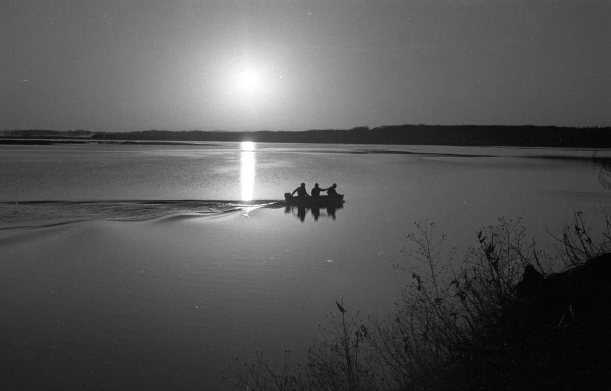 Three boaters shadowed against the dawn carved a quiet wake across the stillness of Manistee Lake this morning. The photo was published in the News Advocate onApril 9,1981. (Manistee County Historical Museum photo)