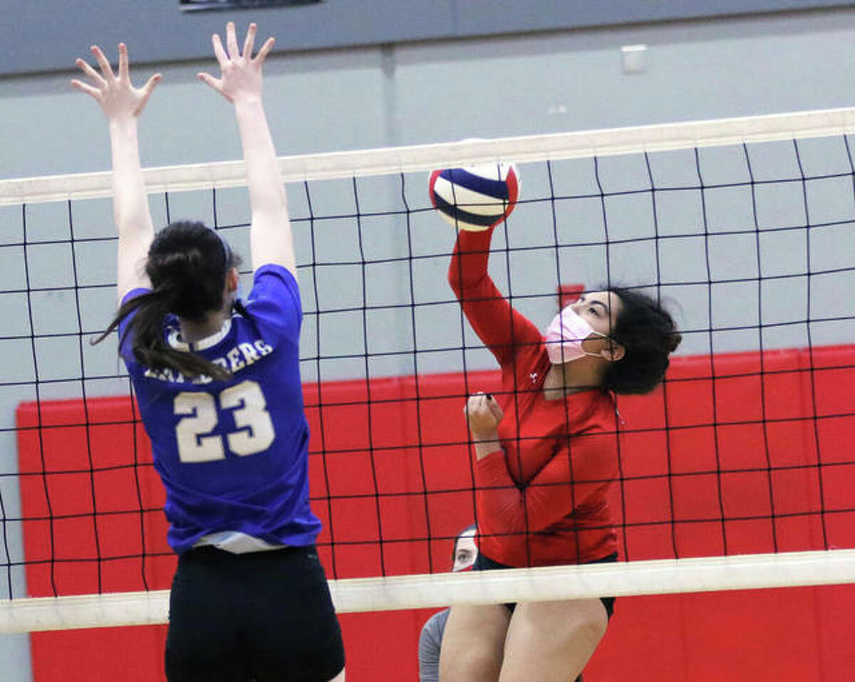 Alton's Taryn Wallace, shown hitting against the block by Marquette Catholic's Abby Williams (23) in at March 27 match in Godfrey, had five kills in the Redbirds' SWC Tourney win over East St. Louis on Wednesday.
