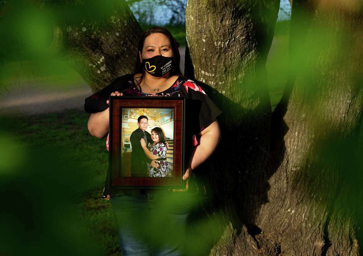 Adelina Rodriguez-Mata poses for a photograph with a picture of her late husband - Raymond Mata - at Ladybird Trail on Thursday, April 1, 2021, in Austin, Texas. Rodriguez-Mata lost her husband to COVID. For a while, she blamed herself for giving it to him.