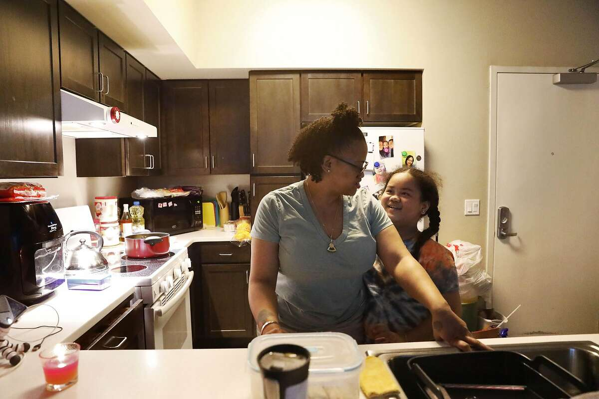 Diana Rosemon (left) talks with her daughter Fraciana Saephan, 7, at their home on Thursday, March 25, in Emeryville, Calif.
