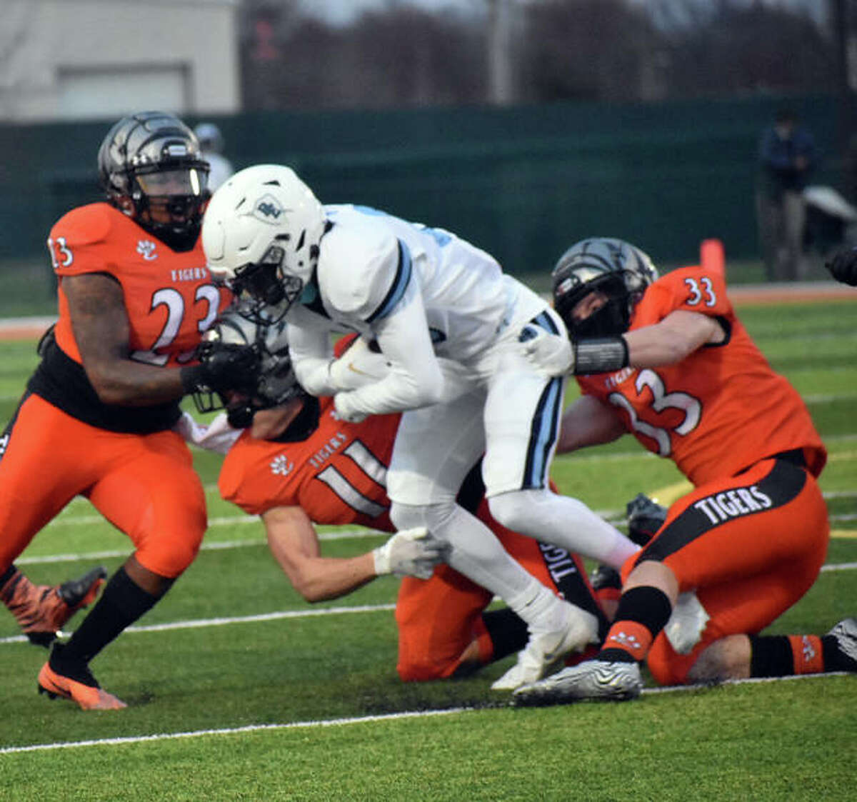 Edwardsville's Cameron Lovett, left, Mason Ahlers, center, and Dalton Brown, right, combine to tackle the Belleville East ball carrier.