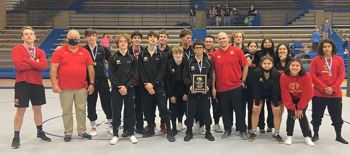 The Caney Creek wrestling team, coached by Jacob Ferguson, poses for a photo after the District 12-5A wrestling meet Wednesday, April 7, 2021 in Houston.