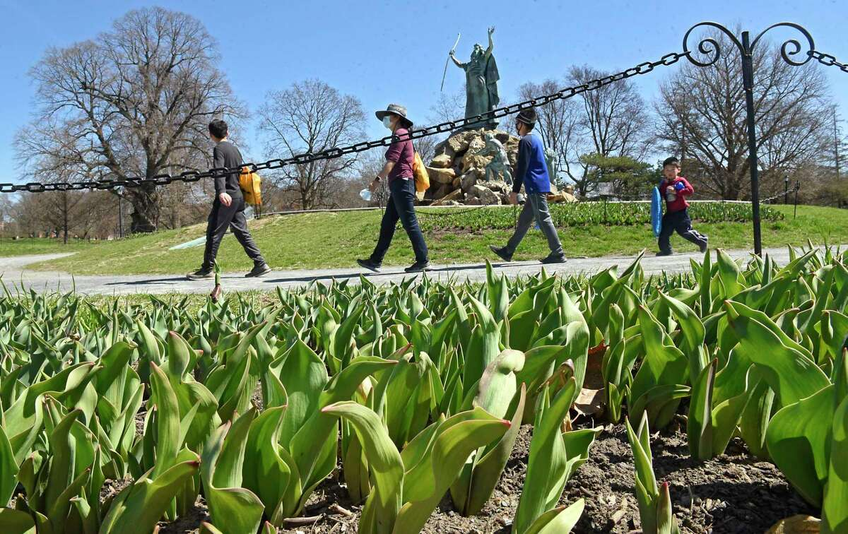 A family walks by beds of soon-to-be blooming Tulips in Washington Park on Thursday, April 8, 2021 in Albany, N.Y. Albany's Annual Tulip Fest will be virtual this year. (Lori Van Buren/Times Union)