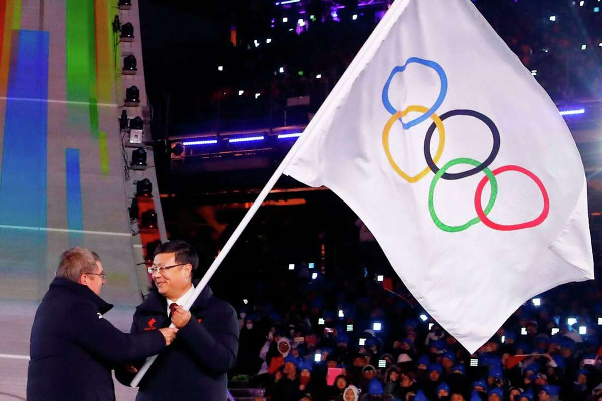 Thomas Bach, left, president of the International Olympic Committee, officially hands over the Olympic flag to Beijing Mayor Chen Jining in 2018.