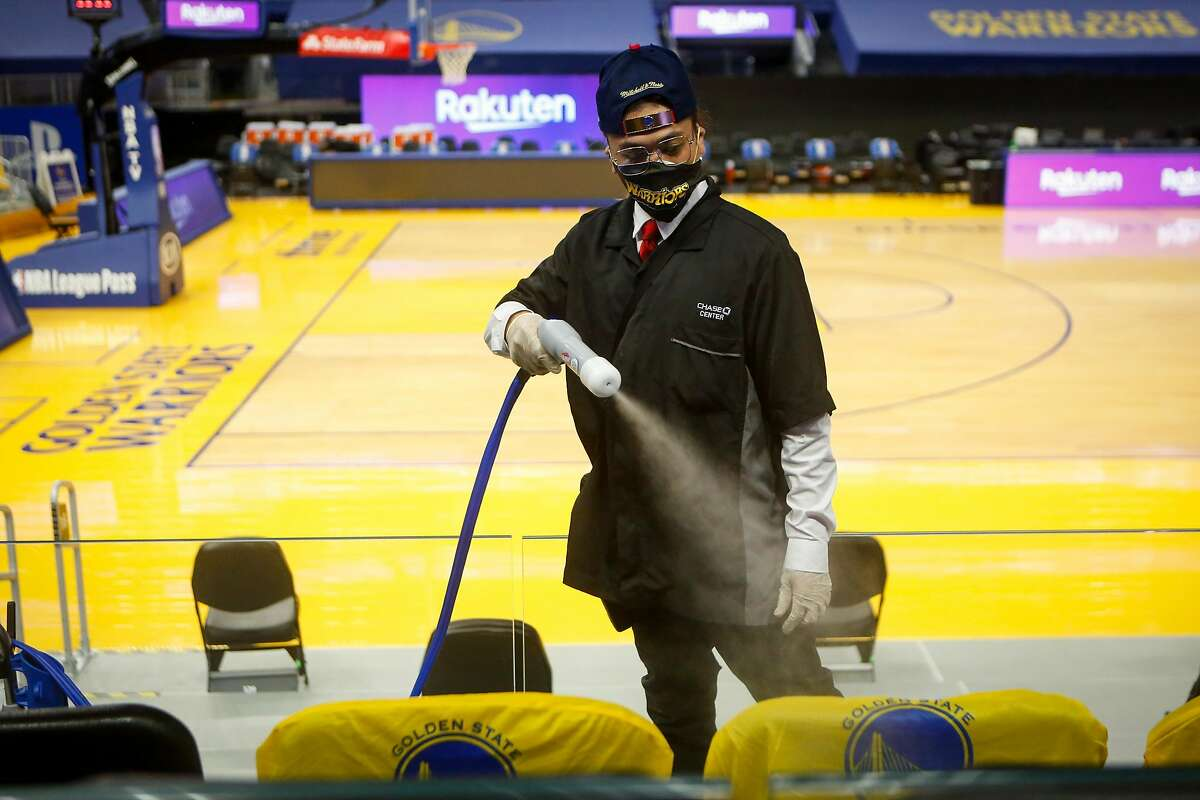 Ryan Tirazona uses an electrostatic sprayer this month to disinfect seats as Chase Center prepares to reopen soon.
