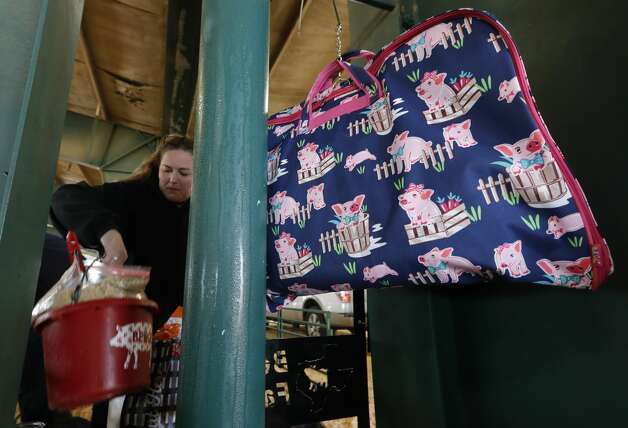 Erin BengeÕs swine-themed bag is seen as she helps her children move their swines into their pens as preparation continues for the return of the Montgomery County Fair and Rodeo, Thursday, April 8, 2021, in Conroe. Future Farms of America students from around the county kicked off the action by moving their swines into the agriculture barn to show. This year, only students will only be able to move their animal into the barn the morning of their animalÕs show as part of the fairÕs COVID-19 safety protocols. Photo: Jason Fochtman/Staff Photographer / 2021 ? Houston Chronicle