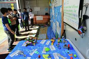 A group of Tracey Elementary School third and fifth-grade students including Mayar Elwerfally, 3rd, Zayn Mir, 3rd, and Angel Contreras, 5th, at right, who created a diorama of Calf Pasture Beach's ecosystem in a shipping container outside the school held tours for other students Wednesday, April 7, 2021, in Norwalk, Conn. The project was one of the school's Service Learning Projects which pairs academic learning with the school's core values.