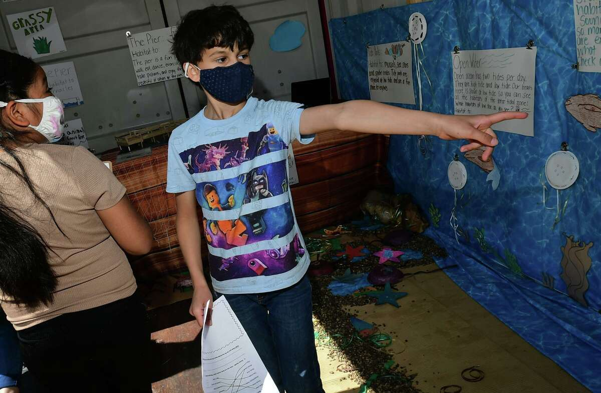 A group of Tracey Elementary School third and fifth-grade students including Zayn Mir, right, who created a diorama of Calf Pasture Beach's ecosystem in a shipping container outside the school held tours for other students Wednesday, April 7, 2021, in Norwalk, Conn. The project was one of the school's Service Learning Projects which pairs academic learning with the school's core values.