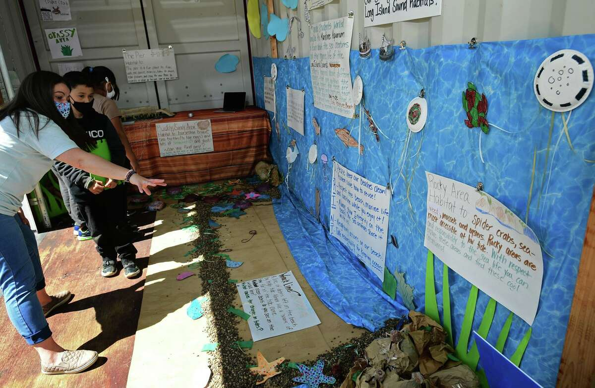 Charadcter Education Magnet Coach Kristen Penta shows 3rd grader Manuel Bautista a diorama made by a group of Tracey Elementary School third and fifth-grade students of Calf Pasture Beach's ecosystem in a shipping container outside the school held tours for other students Wednesday, April 7, 2021, in Norwalk, Conn. The project was one of the school's Service Learning Projects which pairs academic learning with the school's core values.