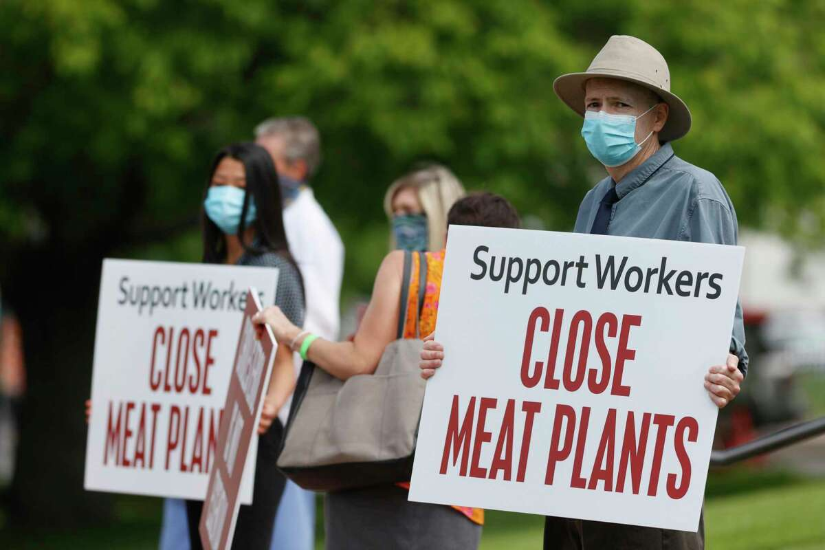 Rob Honish of Denver waves a placard with other protesters outside the State Capitol to call on the governor to close down meat processing plants because of the new coronavirus, Thursday, May 28, 2020, in downtown Denver. The nonprofit Physician's Committee for Responsible Medicine, which represents more than 12,000 doctors, has sent the request to close the packing plants to governors in states that have the facilities. (AP Photo/David Zalubowski)