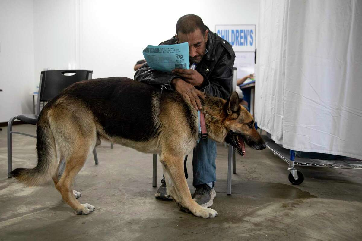 """""""Happy"""" and his dog King wait for 15 minutes after receiving the Johnson & Johnson vaccine at Christian Assistance Ministry. CAM partnered with the San Antonio Fire Department and Metro Health to provide more than 70 vaccines to the unhoused population from around San Antonio. Outreach workers spent the previous day visiting camps to talk to people and convince them to get vaccinated."""