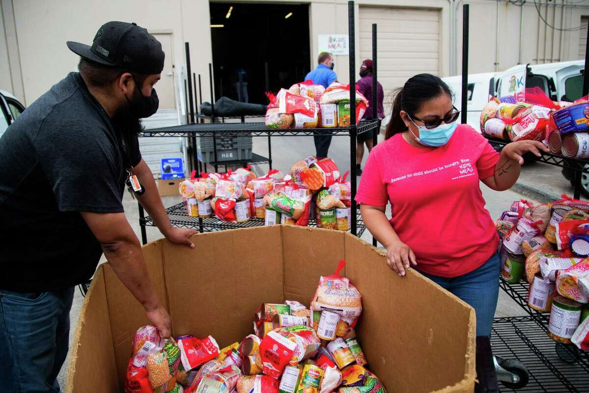 Kids' Meals providers Javier Guerrero, left, and Daisy Niño load up groceries to deliver to families in need in different Houston zip codes, Wednesday, April 7, 2021, in Houston.