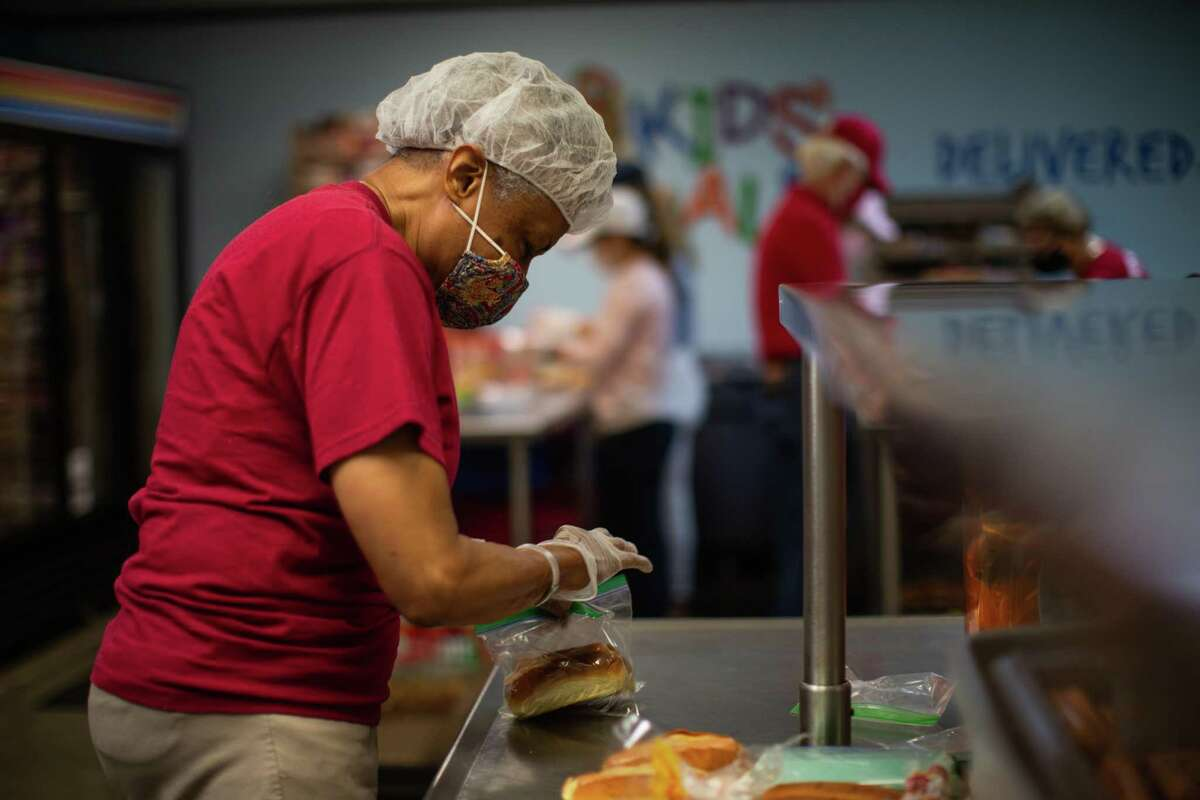 Houston Association of Retired Teachers (HART) member Pat Bonner volunteers at the Kids' Meals making hotdogs to be packed into lunch bags so the lunches can be delivered to children in need of a meal, Wednesday, April 7, 2021, in Houston.
