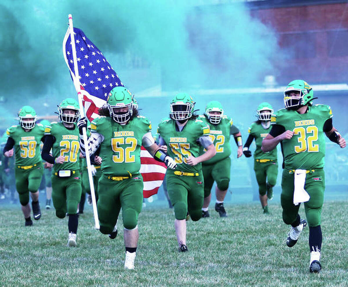 Southwestern's Ashtin Sorgea (52) gets the honor of flag-bearer as fellow seniors Pauly Garrett (20), Collin Campbell (55) and Sam Wolff (32) lead their team onto the field before a March 26 win over Gillespie at Knapp Field in Piasa. The 3-0 Birds play Friday night at Carlinville, seeking to earn both their first winning season and their first victory at Carlinville since 1999.