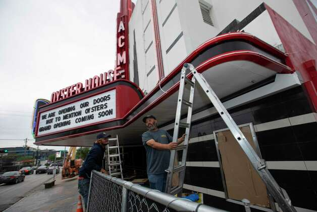 Sign technicians Tre Fairburn, left, and Jacques Silva installing LED rope lights over the marquee at the end of March. Photo: Yi-Chin Lee, Houston Chronicle / Staff Photographer / © 2021 Houston Chronicle