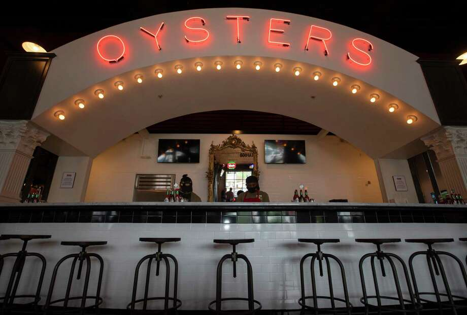 "Acme Oyster House oyster shuckers and trainers Brandon Husley, left, and Tyrus Morris work under the signature ""oysters arch"" on its soft opening day Wednesday, April 7, 2021, in Houston. Husley and Morris came to train new staff from the oyster house's Louisiana locations. Photo: Yi Chin Lee/Staff Photographer / © 2021 Houston Chronicle"