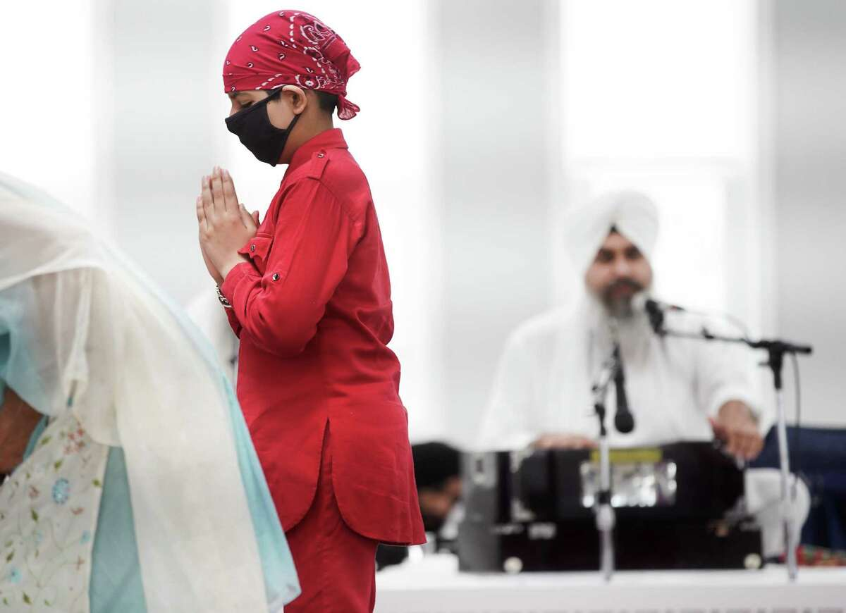 A young Sikh lowers his head in front of the Granth, Sikhism's holy book, during an event at Sikh Center of Gulf Coast in Houston on Saturday, March 27, 2021. The Sikh community is celebrating the 400th anniversary of Guru Tech Bahadur, one of the ten founding gurus of Sikhism.