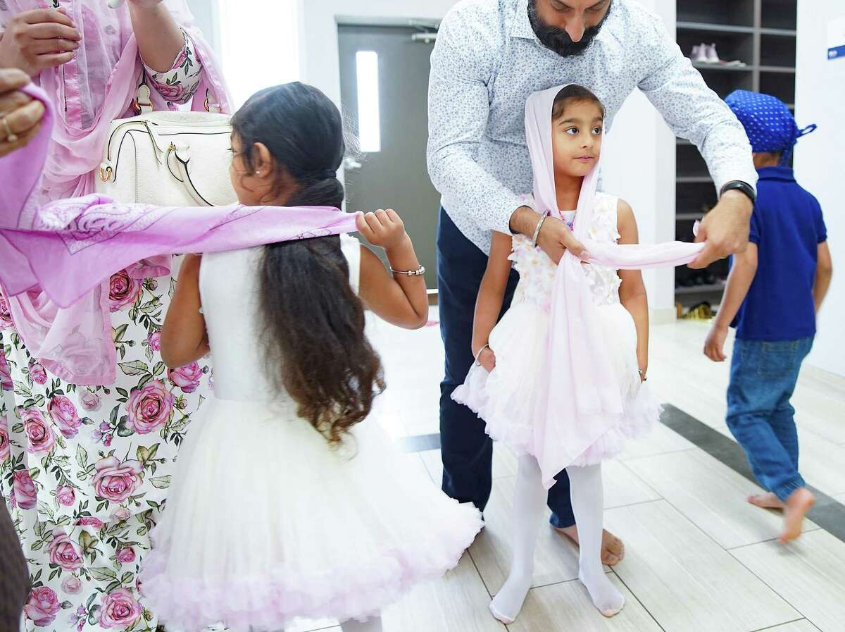 Bikram Singh ties a dupatta on his daughter, Sohiala, 5, before attending a music event at Sikh Center of Gulf Coast in Houston on Saturday, March 27, 2021. The Sikh community is celebrating the 400th anniversary of Guru Tech Bahadur, one of the ten founding gurus of Sikhism.