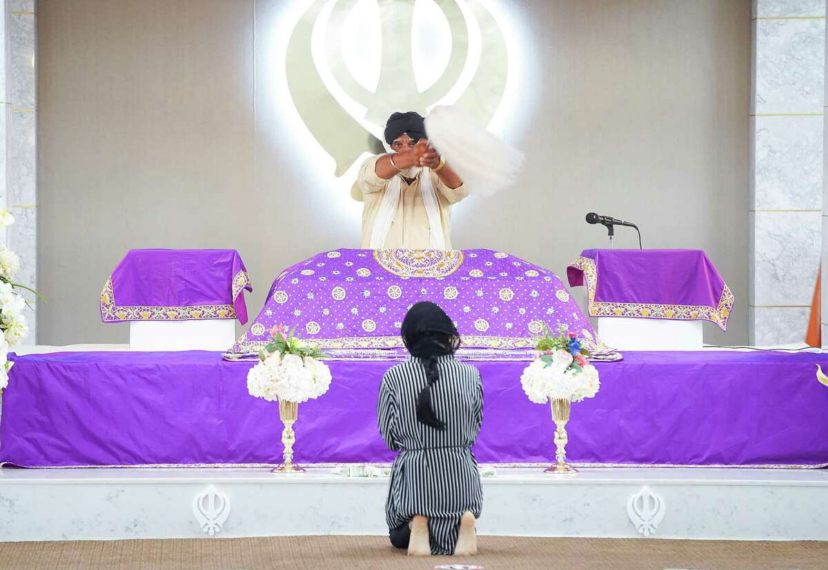 A member of Sikh Center of Gulf Coast waves a chauri over the Granth, Sikhism's holy book, during a concert in the gurdwara in Houston on Saturday, March 27, 2021. The Sikh community is celebrating the 400th anniversary of Guru Tech Bahadur, one of the ten founding gurus of Sikhism.