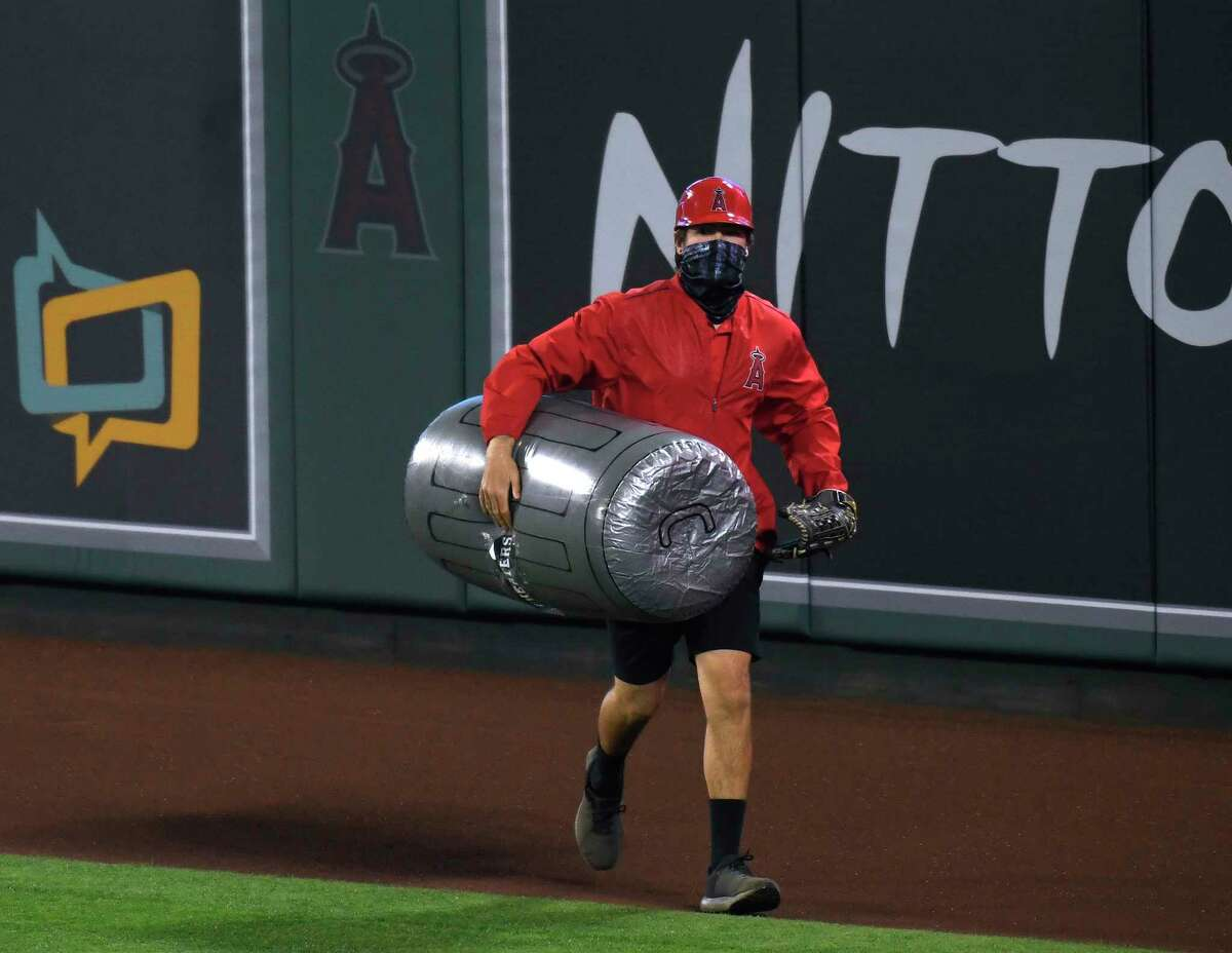 A member of the Los Angeles Angels grounds crew removes an inflated plastic trash can thrown onto the field during the sixth inning against the Houston Astros at Angel Stadium of Anaheim on April 05, 2021, in Anaheim, CA.