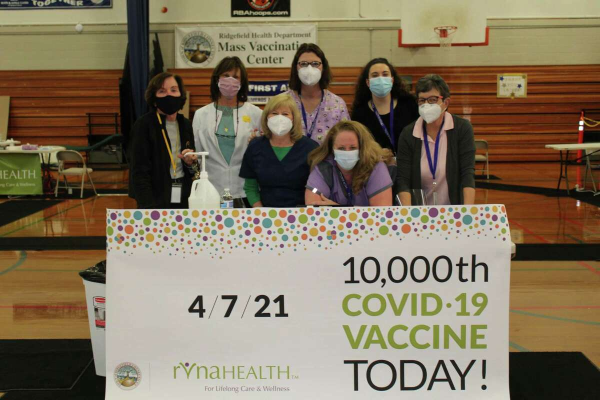 RVNAhealth personnel Meg Spera, Deb Soyak, Ellen Lennon, Christina Tremblay, Leslie Purwin, Lizzie Richards and Jayne Flynn stand by the commemorative banner after administering 10,000 COVID-19 vaccine shots at Ridgefield's collaborative clinic.