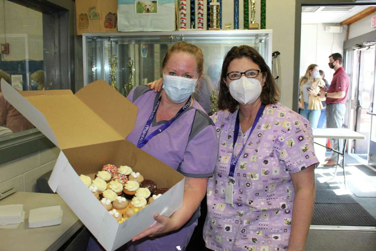 RVNAhealth's Leslie Purwin and Christina Tremblay model the delectable baked goods donated by The Cake Box to commemorate the town's vaccine clinic distributing 10,000 COVID-19 vaccine shots.