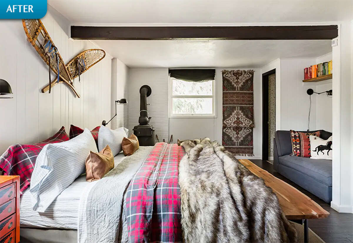 AFTER: Bright white paint completely transforms the space, while the large bed visually reclaims it as the cabin's primary bedroom. A cozy reading area is tucked in an alcove near the woodburning stove.