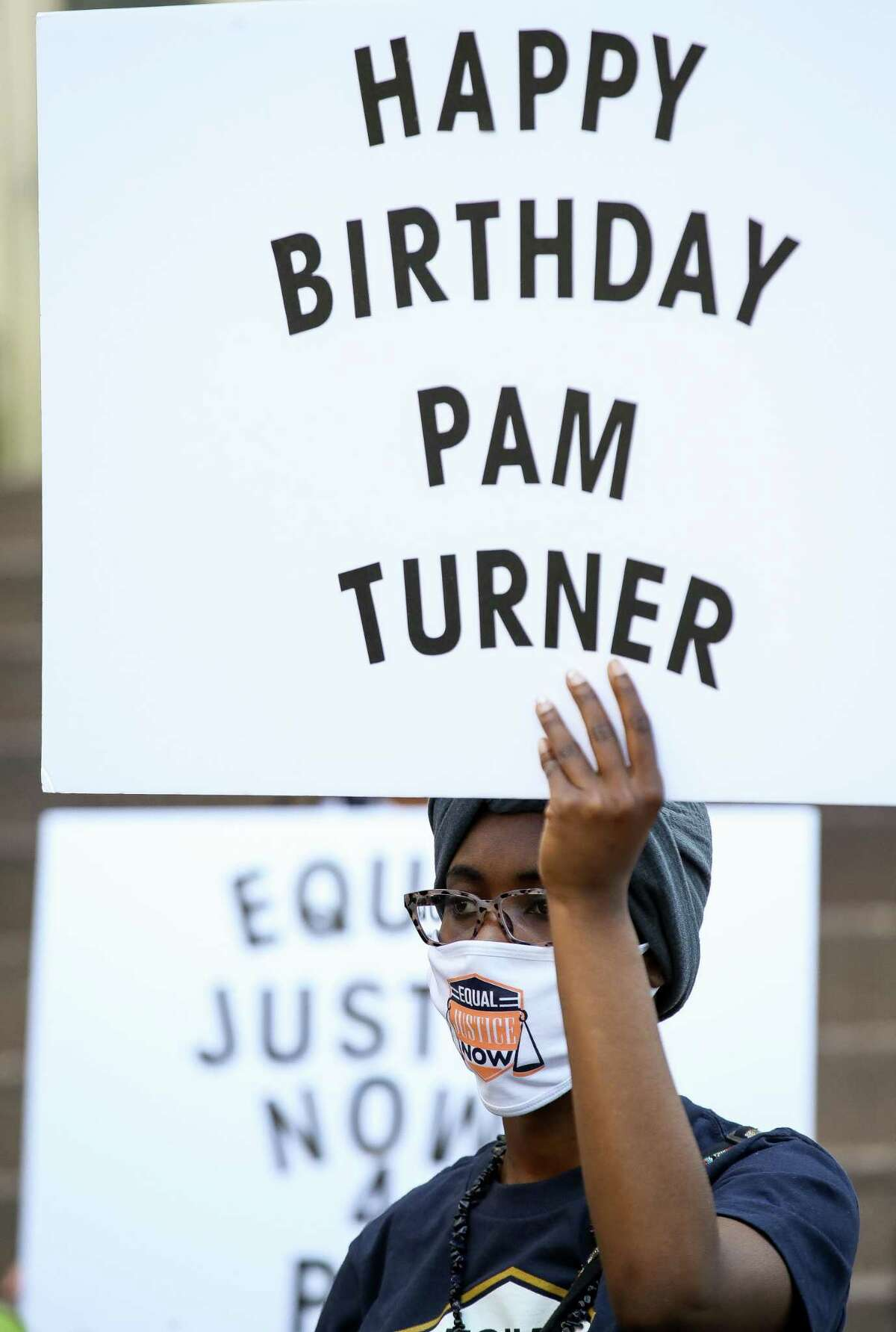 Lauren Bragner holds up a sign for Pamela Turner during a press conference in which attorney Benjamin Crump announced the filing of a federal lawsuit against Baytown Police officer Juan Delacruz outside Harris County Civil Courthouse on Thursday, April 8, 2021, in Houston. Turner, who would have turned 46 years old today, was shot and killed on May 13, 2019.