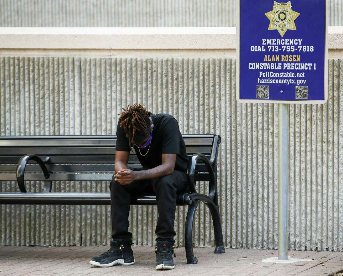 Cameron January sits alone after walking away from the press conference when the death of Pamela Turner - his mother -was being discussed in detail outside the Harris County Civil Courthouse on Thursday, April 8, 2021, in Houston. Attorney Benjamin Crump announced the filing of a federal lawsuit against Baytown Police officer Juan Delacruz in Turner's death, who was shot and killed on May 13, 2019.